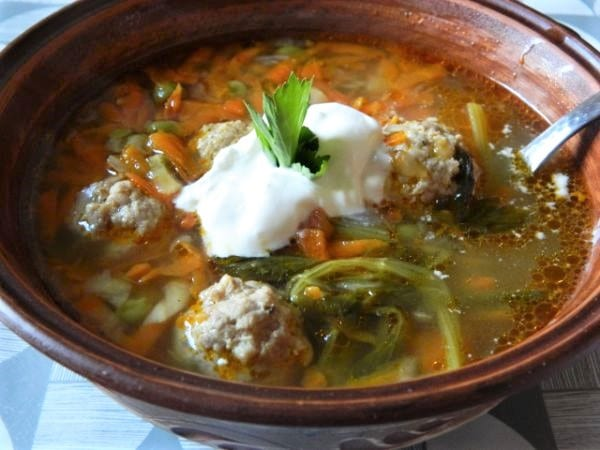 Pork meatballs vegetable soup, served with sour cream.