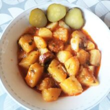 Potato stew with smoked sausages served with pickled cucumber