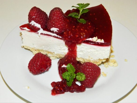 Best Raspberry Cheesecake Recipe-Cheesecake Slice on the Plate With Raspberry Jam on the Top