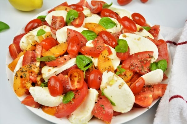 Tomatoes Caprese Salad Recipe-Served on Plate With Basil and Mozzarella
