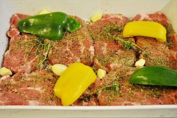 Easy Oven Baked Pork Steak Recipe-Cut Bell Peppers on Seasoned Pork Neck Slices