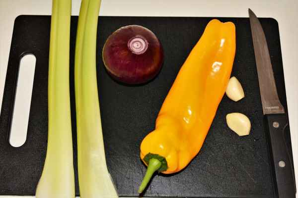 Best Chicken Casserole Recipe-Celery Stalks, Yellow Pepper, Garlic Cloves and Red Onion on the Chopping Board