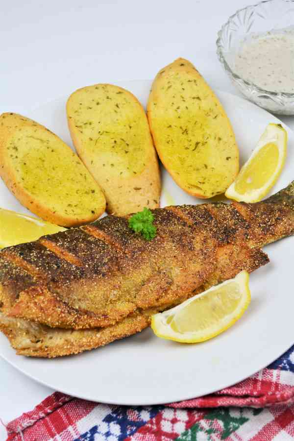 Pan-Fried Rainbow Trout Recipe-Fried Trout Served on Plate With Lemon and Garlic Bread